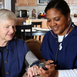 caregiver checking patients vitals